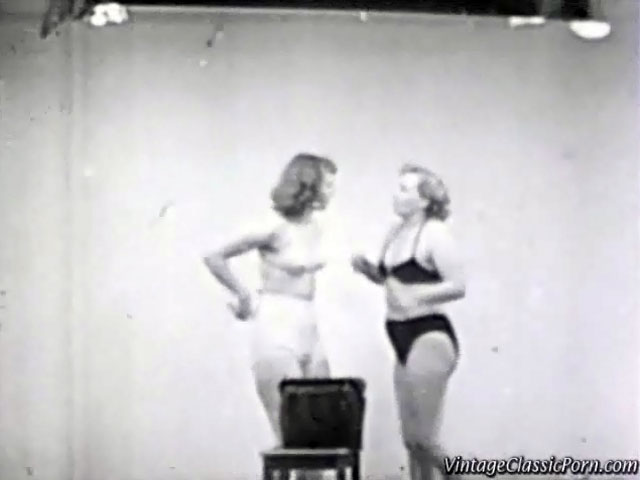 In this vintage movie we see two girls in bikini fighting with each other in a studio. They try to wrestle each other to the floor. In the second part we see two female wrestlers fighting each other in the ring.